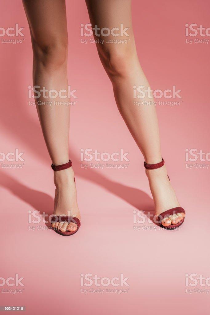 recadrée tir de jambes de femme en élégantes sandales talons hauts sur fond rose - Photo de A la mode libre de droits