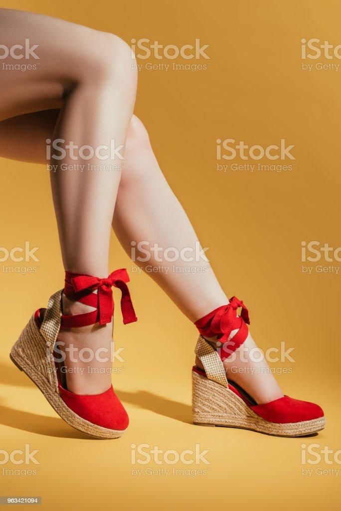 recadrée tir de jambes de femme en sandales à plateforme élégant sur fond jaune - Photo de A la mode libre de droits