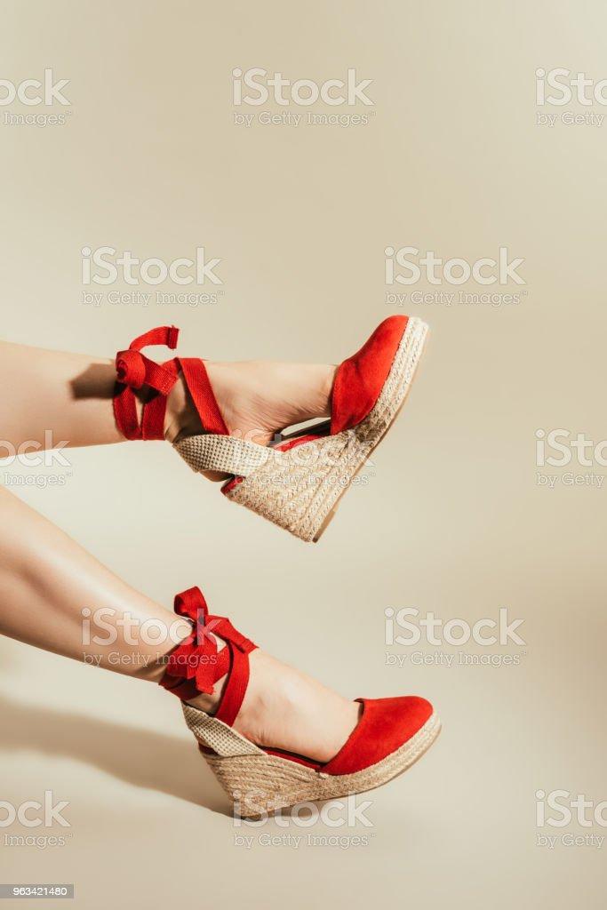recadrée tir de jambes de femme en sandales à plateforme rouge élégant sur fond beige - Photo de A la mode libre de droits