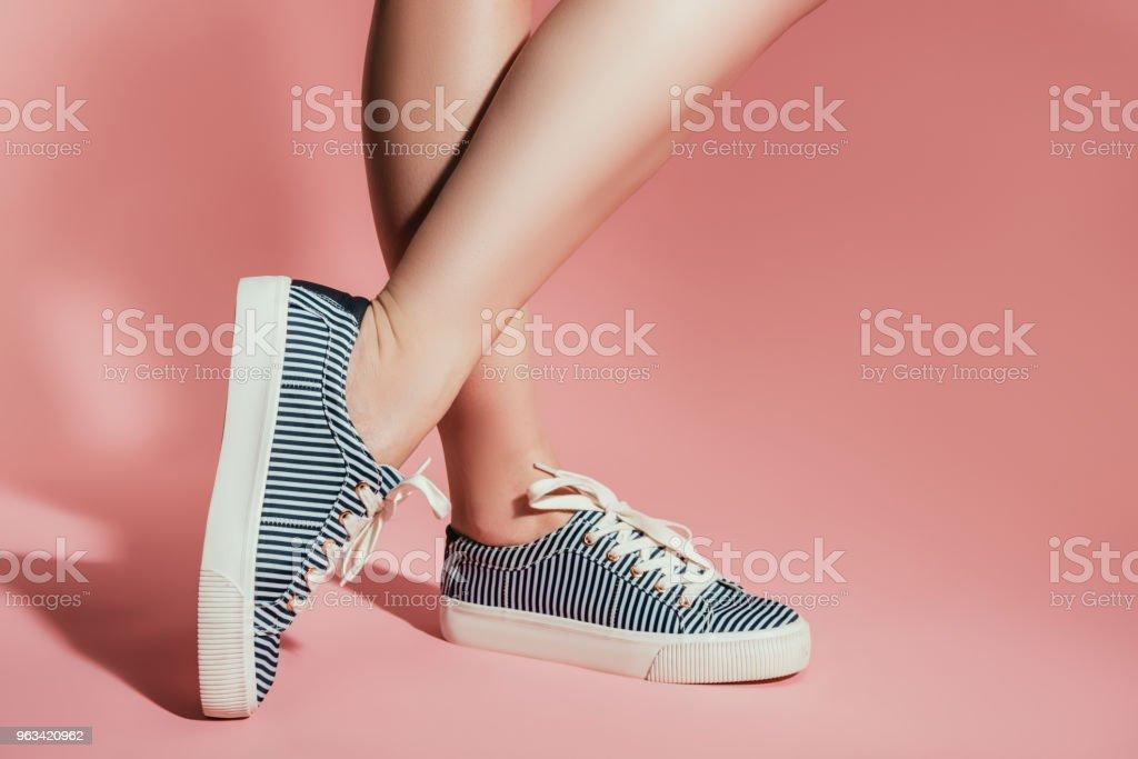 recadrée tir des jambes de femme en élégantes baskets sur fond rose - Photo de A la mode libre de droits