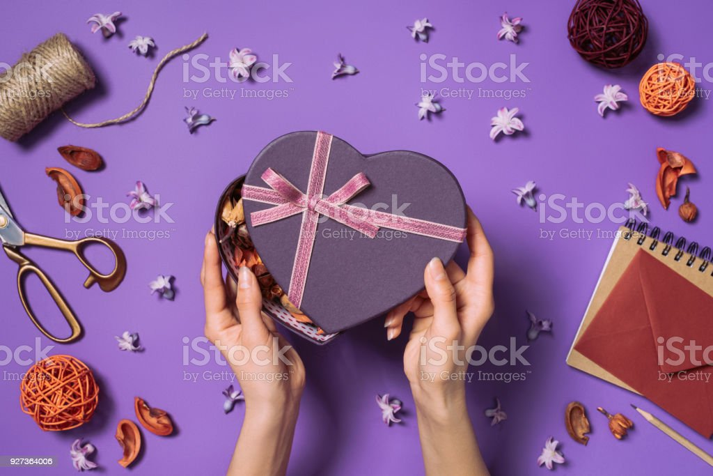 cropped shot of woman opening heart shaped gift isolated on purple cropped shot of woman opening heart shaped gift isolated on purple Adult Stock Photo