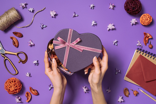 Cropped Shot Of Woman Opening Heart Shaped Gift Isolated On Purple Stock Photo - Download Image Now