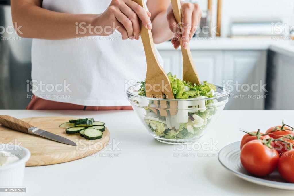 美味しいヘルシーなサラダを準備する女性のショットをトリミング ストックフォト
