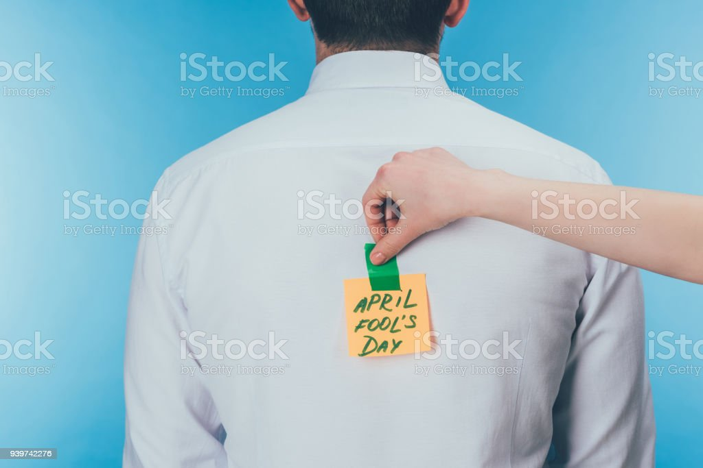 cropped shot of woman putting note with april fools day lettering on males back, april fools day concept stock photo