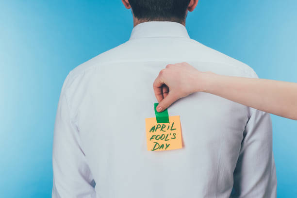 cropped shot of woman putting note with april fools day lettering on males back, april fools day concept cropped shot of woman putting note with april fools day lettering on males back, april fools day concept april fools day stock pictures, royalty-free photos & images