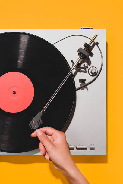 cropped shot of woman turning on vinyl player isolated on yellow - record stock pictures, royalty-free photos & images