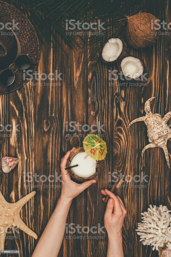 cropped shot of woman with coconut cocktail and cigar on wooden surface surrounded with various tropical travel attributes stock photo
