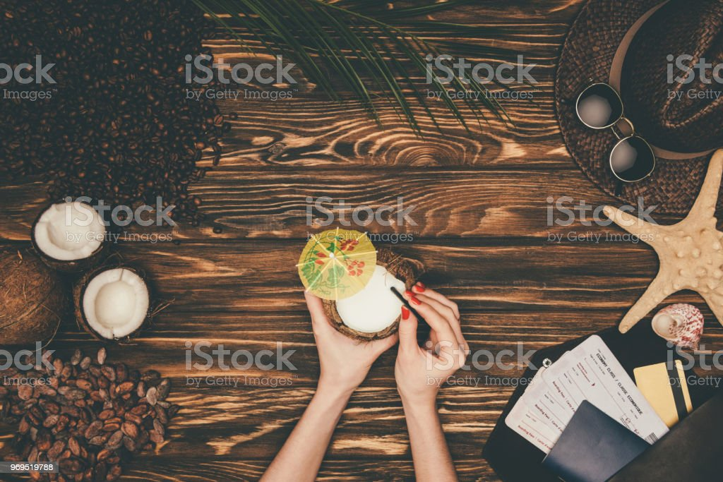 cropped shot of woman with coconut cocktail surrounded with various tropical travel attributes on wooden surface stock photo