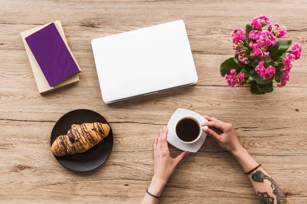 foto von frau mit tasse kaffee am tisch mit laptop, bücher und ein croissant auf platte abgeschnitten - kaffeetasse tattoo stock-fotos und bilder
