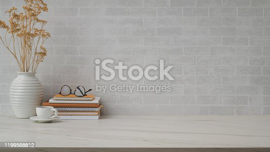 Cropped shot of simple workspace with copy space, vase, tea cup, eyeglasses and books on marble desk with  brick wall background
