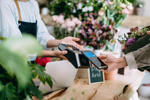 Cropped shot of young Asian man shopping at the flower shop. He is paying for a bouquet with his smartphone, scan and pay a bill on a card machine making a quick and easy contactless payment. NFC technology, tap and go concept