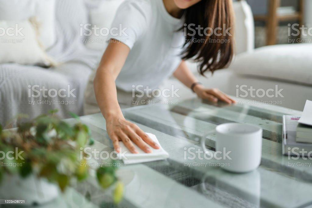 Bijgesneden schot van jonge Aziatische vrouw die de woonkamer opruimt en de koffielijstoppervlakte met een doek afveegt - Royalty-free Aan het werk Stockfoto