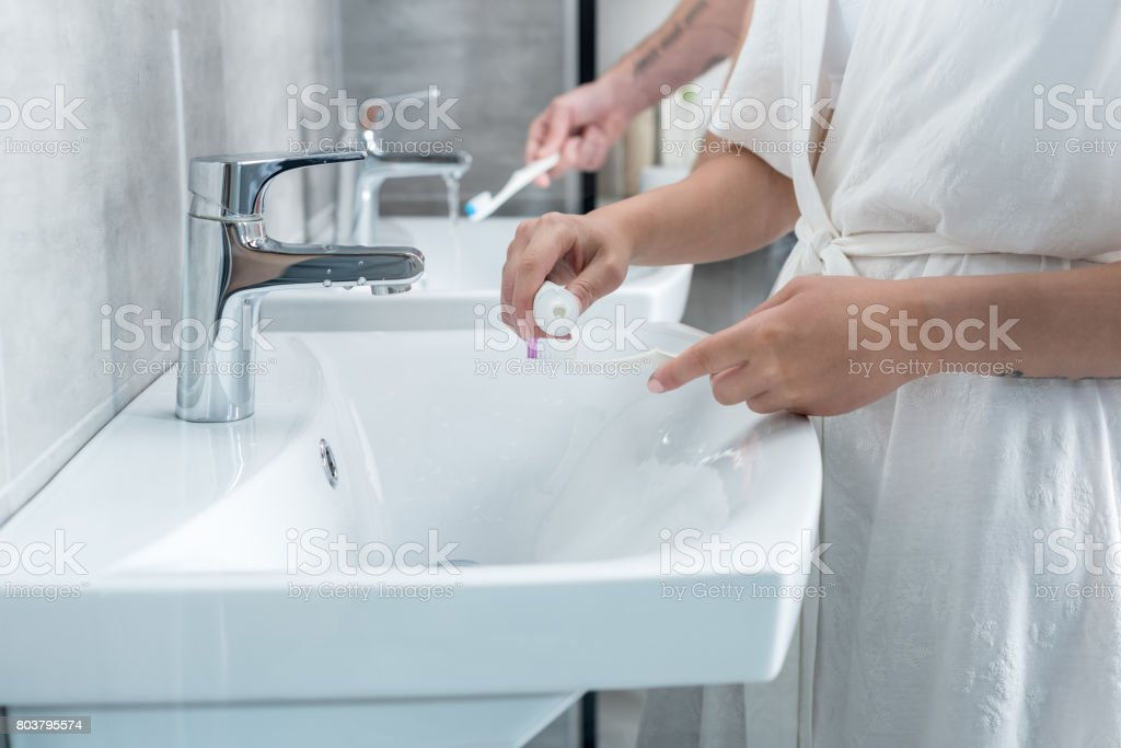 Cropped shot of young couple brushing teeth in bathroom stock photo