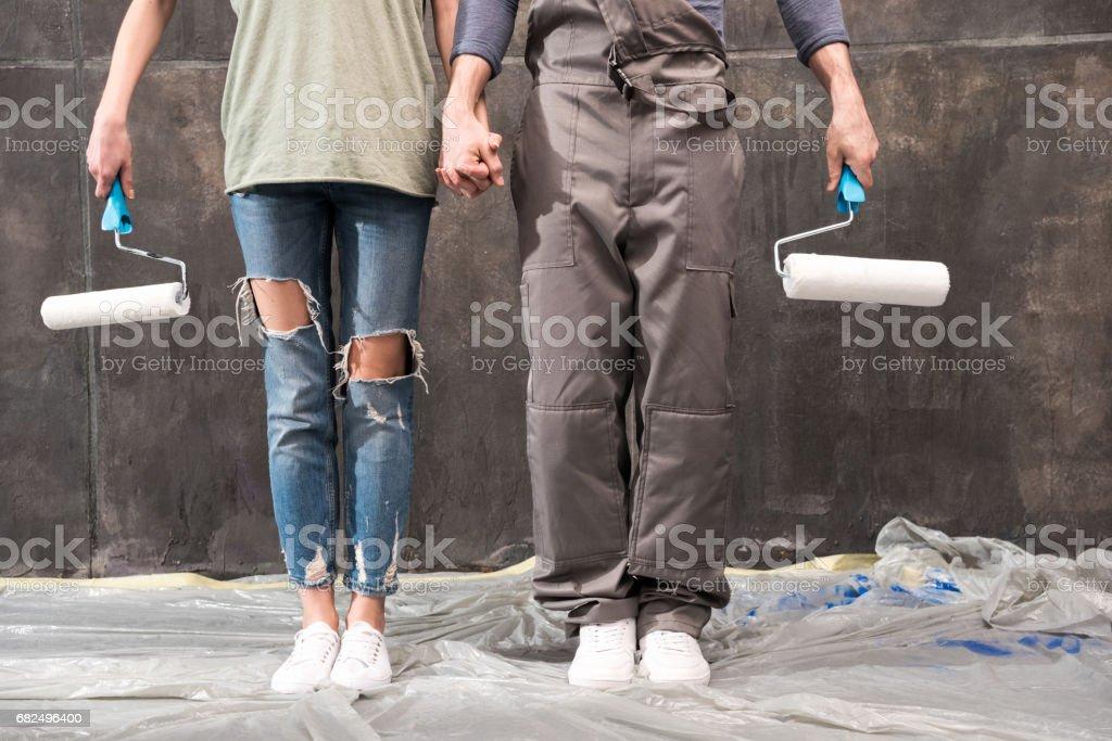 Zugeschnittene Aufnahme des jungen Paares mit Malerrollen Hand in Hand, Renovierung-Konzept Lizenzfreies stock-foto