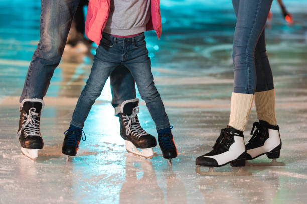 cropped shot of young family in skates skating together on rink cropped shot of young family in skates skating together on rink ice skating stock pictures, royalty-free photos & images