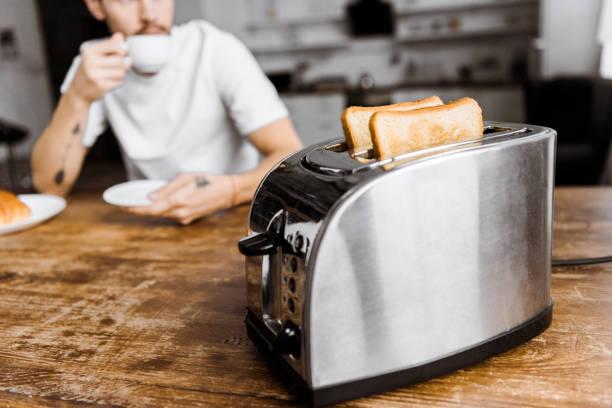 Schuss des Jünglings Kaffeetrinken zu Hause mit dem Toaster auf Vordergrund beschnitten – Foto