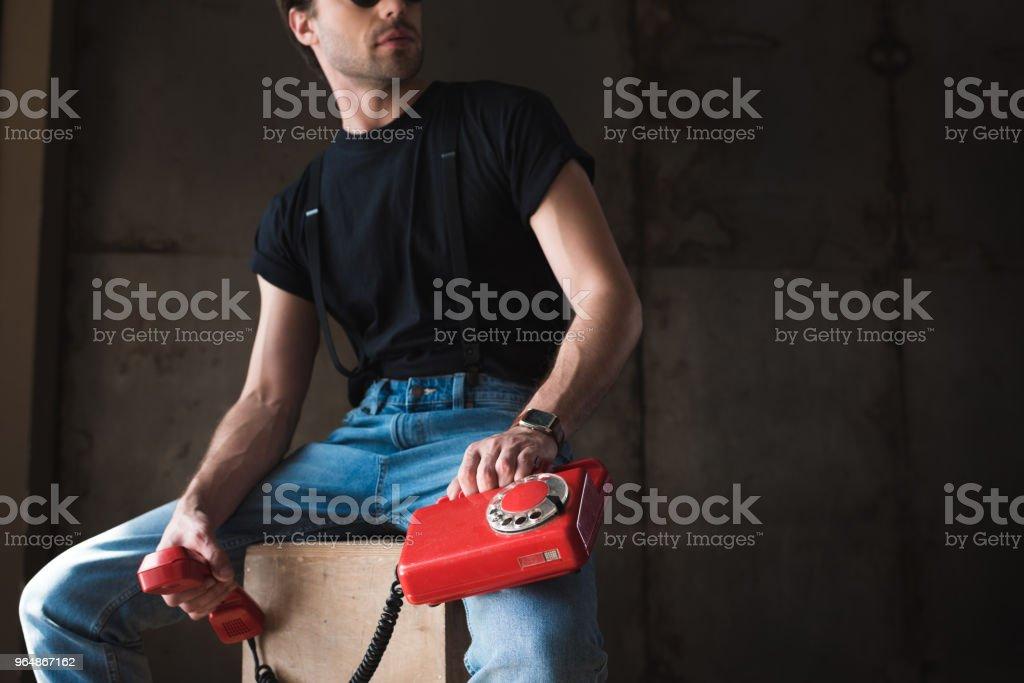 黑色 t恤和吊帶與復古有線紅色手機的年輕人裁剪拍攝 - 免版稅T恤圖庫照片