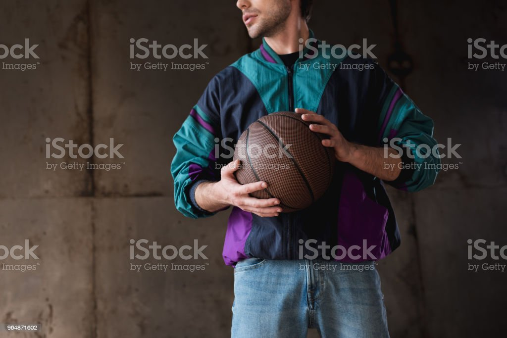 cropped shot of young man in vintage windcheater with basketball ball royalty-free stock photo