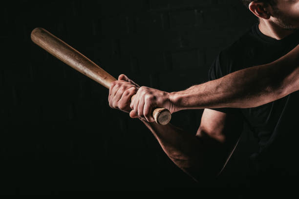 cropped shot of young man playing baseball with bat isolated on black - baseball bat stock photos and pictures