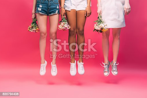 istock cropped shot of young multiethnic women holding flowers and jumping isolated on pink 835794408
