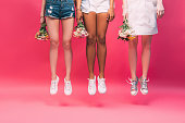 cropped shot of young multiethnic women holding flowers and jumping isolated on pink