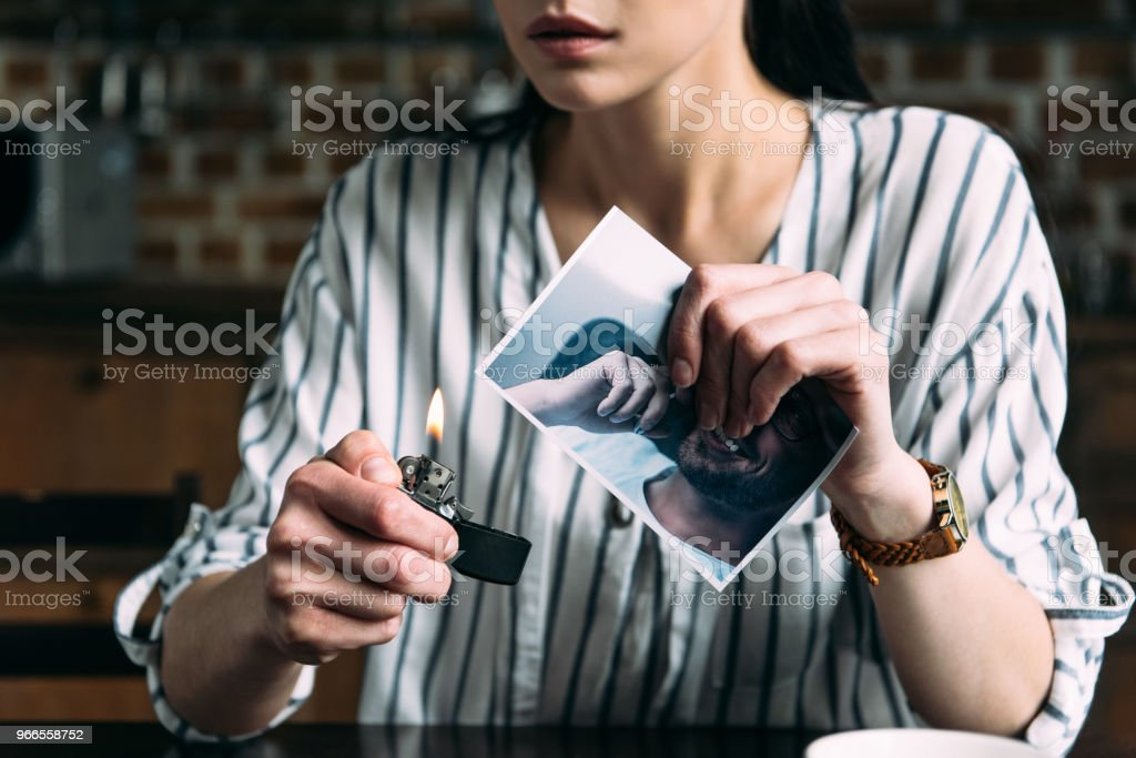 cropped shot of young woman burning photo card of ex-boyfriend stock photo
