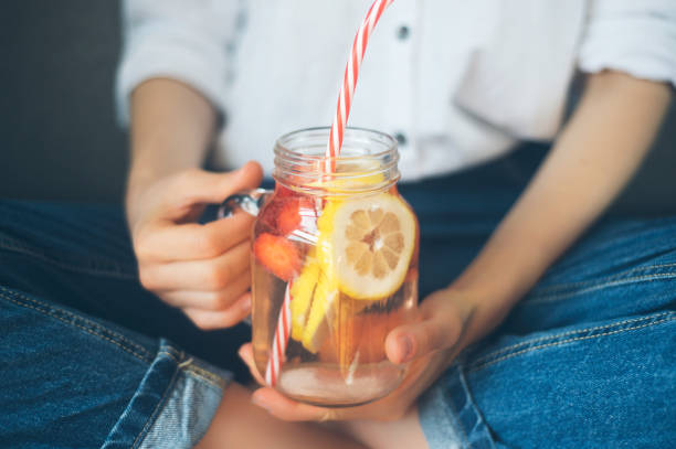 cropped shot of young woman drinking home made fresh summer drink from mason jar with straw cropped shot of young woman drinking home made fresh summer drink from mason jar with straw lemon fruit stock pictures, royalty-free photos & images