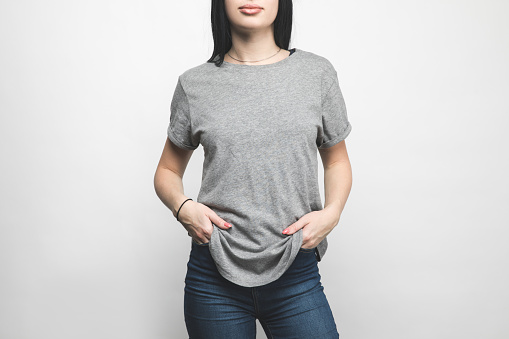 cropped shot of young woman in blank grey t-shirt on white