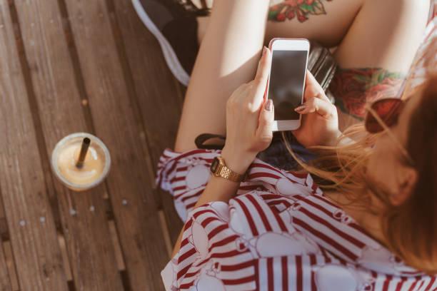 aufnahme der jungen frau mit smartphone auf holzboden im freien sitzend beschnitten - essen tattoos stock-fotos und bilder