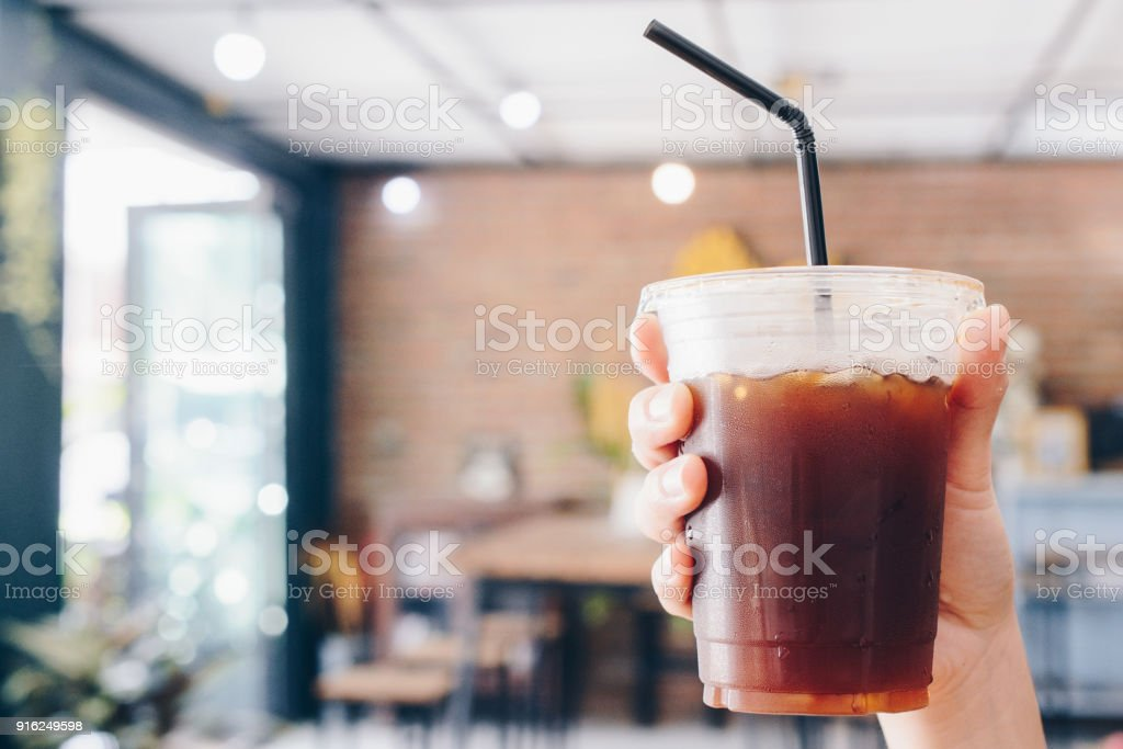 Cropped shot view of human holding a cup of Ice Americano. – zdjęcie