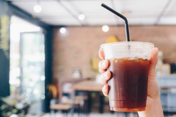 Cropped shot view of human holding a cup of Ice Americano. stock photo