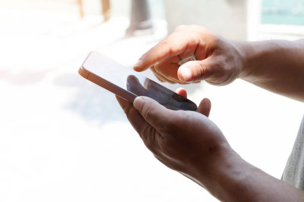 Cropped shot view of man's hands holding smart phone stock photo