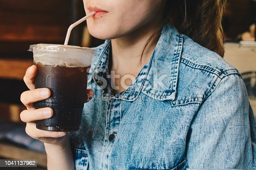 Shot of woman drinking iced black coffee.