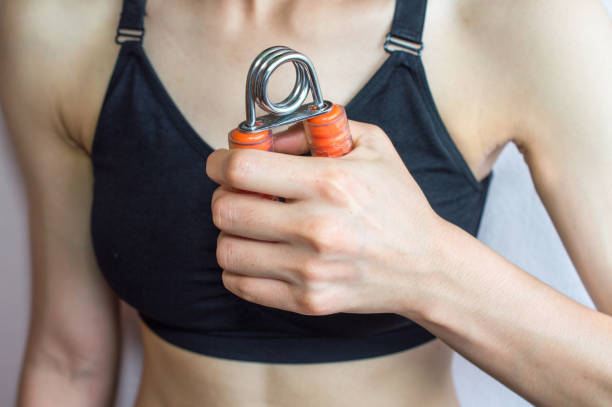 cropped shot view of woman handle a hand grip for exercise with white wall background. - hand grip stock photos and pictures