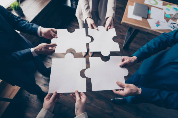 Cropped top above high angle view of stylish elegant sharks holding in hands fitting big large puzzle pieces together team building in loft industrial interior work place station stock photo