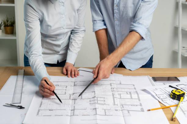 자른된 두 명의 작성기 사람 전문 디자이너 분배기 연필 눈금자 측정 테이블에 워크스테이션에 formalwear 셔츠 서 토론 전문 분석 검사 체계 종이 서류 확인 - 청사진 뉴스 사진 이미지