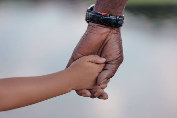 cropped view of african american grandfather holding hands with granddaughter stock photo