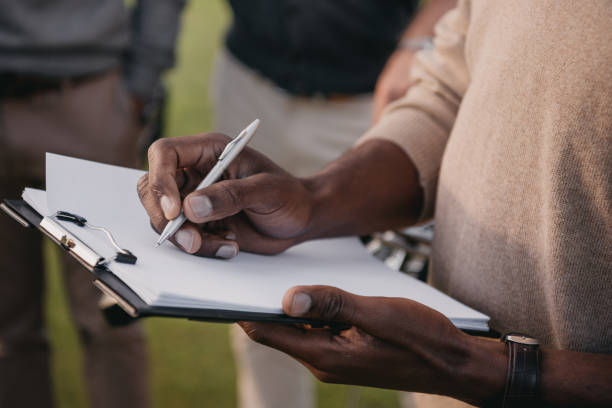 cropped view of african american man writing something on paper in clipboard stock photo
