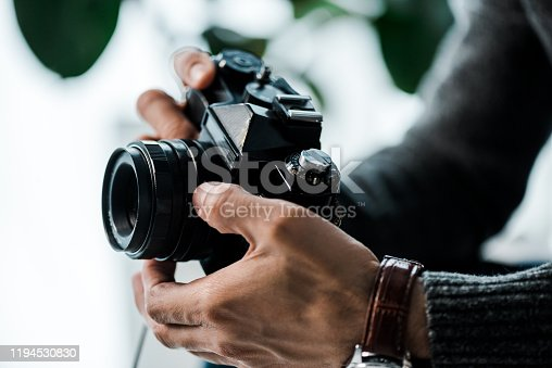 cropped view of bi-racial man holding digital camera in apartment