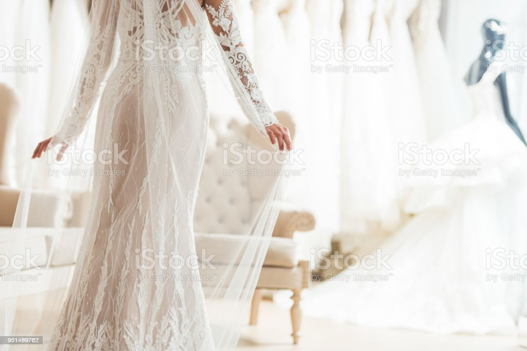 Cropped view of bride in lace dress in wedding salon stock photo