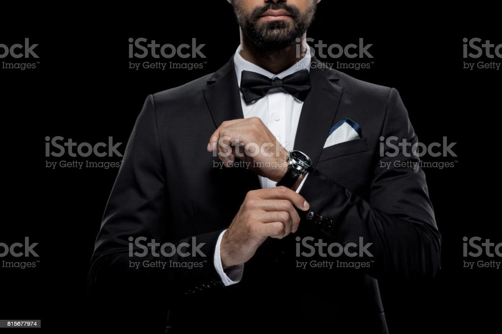 cropped view of businessman in bow tie and tuxedo with watch, isolated on black stock photo