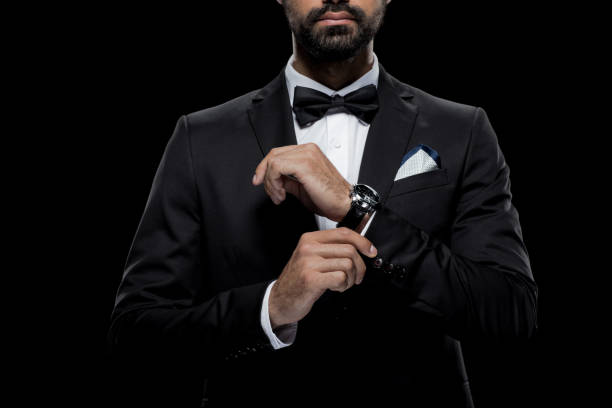 cropped view of businessman in bow tie and tuxedo with watch, isolated on black - tuxedo stock photos and pictures