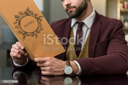 cropped view of businessman in formal wear sitting at restaurant and holding menu