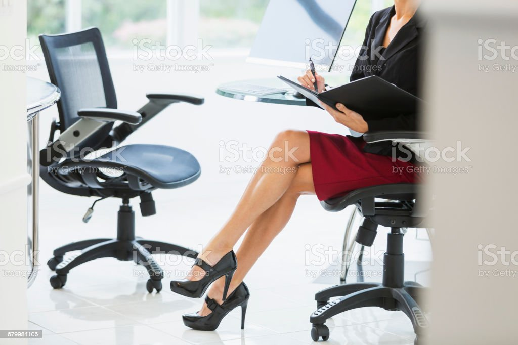 Cropped view of businesswoman in office taking notes stock photo