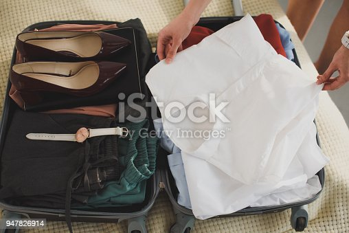 istock cropped view of businesswoman packing clothes in suitcase for business trip 947826914