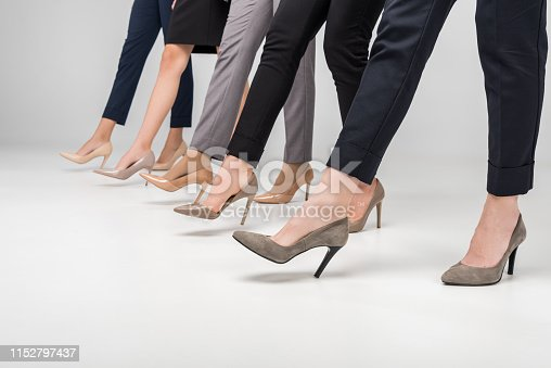 cropped view of businesswomen walking in high heel shoes on grey background