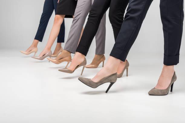 bijgesneden weergave van ondernemers wandelen in hoge hak schoenen op grijze achtergrond - hoge hakken stockfoto's en -beelden