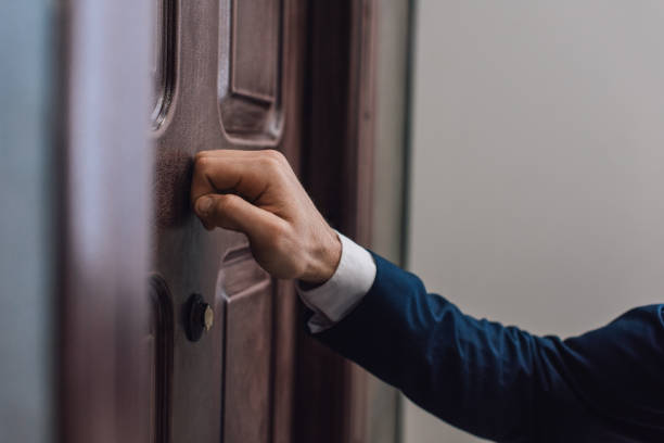 Cropped view of collector knocking on door with hand stock photo