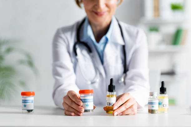 cropped view of doctor in white coat holding bottles with cbd and medical cannabis lettering stock photo