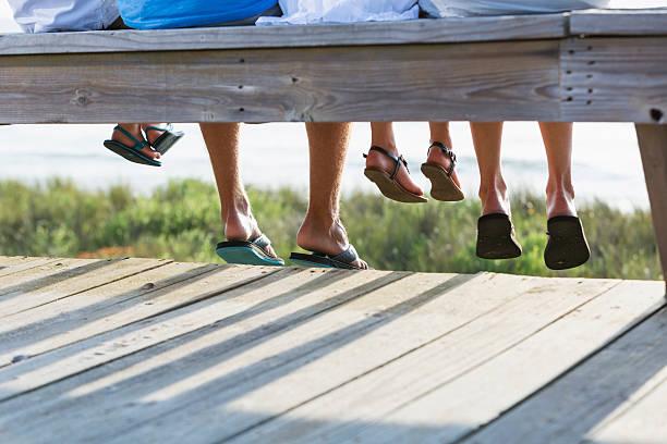 zugeschnittene ansicht familie am strand - sitzbank schuhe stock-fotos und bilder